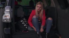 Το κορίτσι βάζει στα παπούτσια στο αυτοκίνητο φιλμ μικρού μήκους