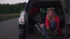 Το κορίτσι βάζει στις κάλτσες στο αυτοκίνητο φιλμ μικρού μήκους