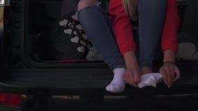 Το κορίτσι βάζει στις κάλτσες στο αυτοκίνητο απόθεμα βίντεο