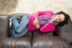 Το κορίτσι βήχει και βρίσκεται στον καναπέ Στοκ Εικόνες