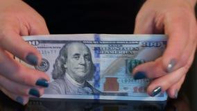 Το κορίτσι βγάζει έναν σωρό των δολαρίων από τον πίνακα, κινηματογράφηση σε πρώτο πλάνο φιλμ μικρού μήκους