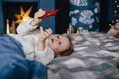 Το κορίτσι βρίσκεται σε ένα κρεβάτι και μια εκμετάλλευση ένα κόκκινο αστέρι, διακοσμήσεις για το χριστουγεννιάτικο δέντρο Στοκ φωτογραφία με δικαίωμα ελεύθερης χρήσης