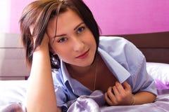 Το κορίτσι βρίσκεται σε ένα κρεβάτι στο θεατή Στοκ Φωτογραφία