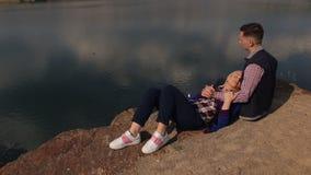 Το κορίτσι βρίσκεται στα πόδια ενός τύπου στην όχθη ποταμού απόθεμα βίντεο