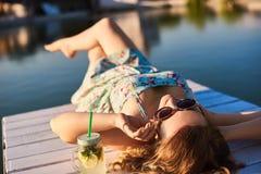 Το κορίτσι βρίσκεται στην ξύλινη αποβάθρα πέρα από το νερό με τις προσοχές μου ιδιαίτερες και που απολαμβάνουν τη θερμή θερινή ηλ Στοκ εικόνες με δικαίωμα ελεύθερης χρήσης