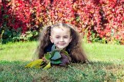 Το κορίτσι βρίσκεται στη χλόη με τα φύλλα φθινοπώρου στα χέρια Στοκ εικόνες με δικαίωμα ελεύθερης χρήσης