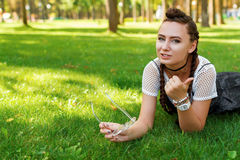 Το κορίτσι βρίσκεται στη χλόη στο πάρκο με τα γυαλιά ηλίου στο χέρι του Στοκ Εικόνες