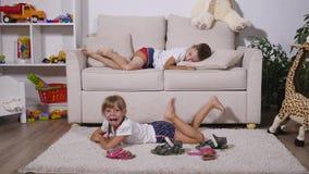 Το κορίτσι βρίσκεται στον τάπητα, και το αγόρι στον καναπέ απόθεμα βίντεο