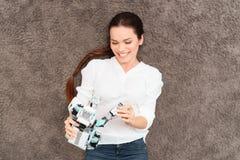 Το κορίτσι βρίσκεται στο γκρίζο πάτωμα και κρατά ένα ρομπότ ρινοκέρων στα χέρια της Θέτει και χαμογελά Στοκ εικόνα με δικαίωμα ελεύθερης χρήσης