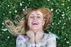 Το κορίτσι βρίσκεται στο ξέφωτο λουλουδιών Στοκ Εικόνα