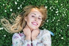Το κορίτσι βρίσκεται στο ξέφωτο λουλουδιών Στοκ Εικόνες