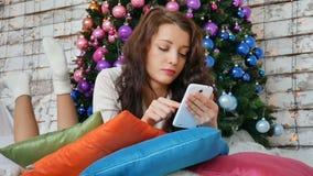 Το κορίτσι βρίσκεται στο πάτωμα με το τηλέφωνο στα χέρια της στο σπίτι στο υπόβαθρο ενός χριστουγεννιάτικου δέντρου απόθεμα βίντεο