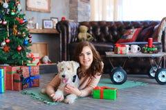 Το κορίτσι βρίσκεται στο πάτωμα στο καρό που αγκαλιάζει το σκυλί, που χαμογελά και που θέτει για Στοκ Φωτογραφία