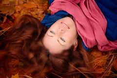 Το κορίτσι βρίσκεται στο φύλλωμα φθινοπώρου στοκ φωτογραφία με δικαίωμα ελεύθερης χρήσης