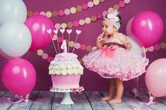 Το κορίτσι γενεθλίων μικρών κοριτσιών ` s λερώθηκε σε ένα κέικ Το πρώτο κέικ Η χρήση του πρώτου κέικ Κέικ συντριβής Στοκ φωτογραφία με δικαίωμα ελεύθερης χρήσης