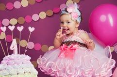 Το κορίτσι γενεθλίων μικρών κοριτσιών ` s λερώθηκε σε ένα κέικ Το πρώτο κέικ Η χρήση του πρώτου κέικ Κέικ συντριβής Στοκ Εικόνες