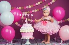 Το κορίτσι γενεθλίων μικρών κοριτσιών ` s λερώθηκε σε ένα κέικ Το πρώτο κέικ Η χρήση του πρώτου κέικ Κέικ συντριβής Στοκ εικόνα με δικαίωμα ελεύθερης χρήσης