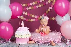 Το κορίτσι γενεθλίων μικρών κοριτσιών ` s λερώθηκε σε ένα κέικ Το πρώτο κέικ Η χρήση του πρώτου κέικ Κέικ συντριβής Στοκ Φωτογραφία
