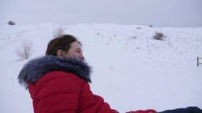 Το κορίτσι γλιστρά μέσα το χειμώνα στο χιόνι από τον υψηλό λόφο στο έλκηθρο και έναν διογκώσιμο σωλήνα χιονιού παιχνίδια κοριτσιώ απόθεμα βίντεο