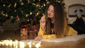 Το κορίτσι γράφει μια επιστολή σε Άγιο Βασίλη, στο υπόβαθρο του χριστουγεννιάτικου δέντρου φιλμ μικρού μήκους