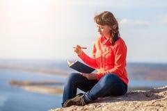 Το κορίτσι γράφει σε ένα σημειωματάριο Στοκ Εικόνα
