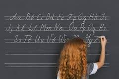 Το κορίτσι γράφει στην κιμωλία σε έναν μαύρο πίνακα στοκ εικόνες