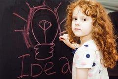 Το κορίτσι γράφει στην κιμωλία σε έναν πίνακα στοκ φωτογραφία