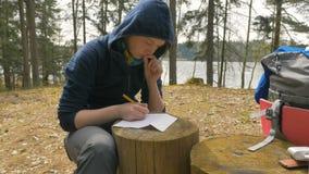 Το κορίτσι γράφει τις σημειώσεις για το κολόβωμα στο δάσος φιλμ μικρού μήκους