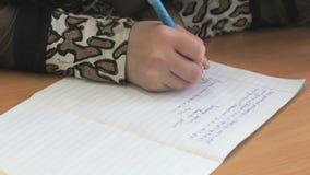 Το κορίτσι γράφει το κείμενο σε ένα copybook χρησιμοποιώντας μια μάνδρα φιλμ μικρού μήκους