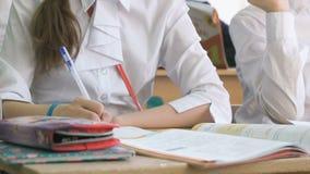 Το κορίτσι γράφει το κείμενο σε ένα copybook χρησιμοποιώντας τη μάνδρα σφαιρών απόθεμα βίντεο