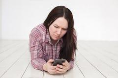Το κορίτσι γράφει sms στο τηλέφωνο, σε απευθείας σύνδεση συνομιλία Στοκ Φωτογραφία