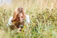 Το κορίτσι γράφει sms στο τηλέφωνο στη χλόη Στοκ Εικόνα