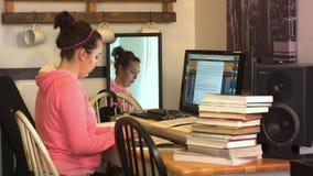 Το κορίτσι γυμνασίου κολλεγίου εξετάζει τα έγγραφα και τους τύπους στον υπολογιστή φιλμ μικρού μήκους