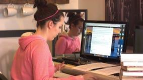 Το κορίτσι γυμνασίου κολλεγίου διαβάζει τα βιβλία γραφικής εργασίας και χρησιμοποιεί το ποντίκι υπολογιστών φιλμ μικρού μήκους