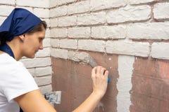 Το κορίτσι γυψαδόρων κάνει τη μίμηση του συντάκτη σχεδιαστών της πλινθοδομής στον τοίχο ενός διαμερίσματος στοκ φωτογραφία