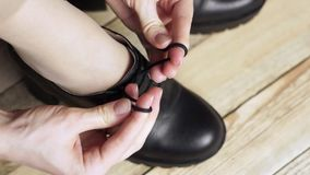 Το κορίτσι δένει τα χέρια η δαντέλλα μπότες απόθεμα βίντεο