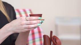 Το κορίτσι δίνει ένα φλυτζάνι του τσαγιού σε μια ξύλινη στάση, η φίλη του, τελετή τσαγιού απόθεμα βίντεο