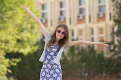 το κορίτσι δίνει ανοικτό της χαμογελώντας ευρέως τις νεολαίες Στοκ Εικόνα