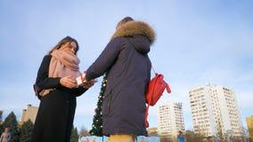 Το κορίτσι δίνει στη φίλη του ένα νέο δώρο έτους κάτω από το δέντρο κίνηση αργή φιλμ μικρού μήκους