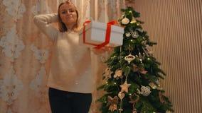 Το κορίτσι δίνει στη φίλη του ένα νέο δώρο έτους κάτω από το δέντρο απόθεμα βίντεο