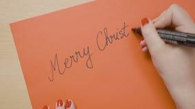 Το κορίτσι δίνει τη Χαρούμενα Χριστούγεννα γραψίματος σε μια κόκκινη κάρτα εγγράφου με το μαύρο δείκτη για να το στείλει στο φίλο φιλμ μικρού μήκους