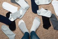 Το κορίτσι δεν μπορεί να αποφασίσει ποιες κάλτσες να φορέσουν, η τοπ άποψη στοκ εικόνα