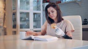 Το κορίτσι διαβάζει και κρατά ένα μπισκότο με το ρομποτικό χέρι της απόθεμα βίντεο
