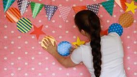 Το κορίτσι διακοσμεί το δωμάτιο για τις διακοπές Ντεκόρ για τον εορτασμό συμβαλλόμενο μέρος γενέθλια ευτυχή φιλμ μικρού μήκους
