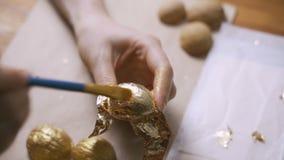 Το κορίτσι διακοσμεί τα καρύδια με το χρυσό Ντεκόρ διακοπών απόθεμα βίντεο
