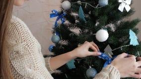Το κορίτσι διακοσμεί τα παιχνίδια χριστουγεννιάτικων δέντρων απόθεμα βίντεο