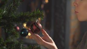 το κορίτσι διακοσμεί το χριστουγεννιάτικο δέντρο σε ένα σπίτι Εορτασμός διακοπών Χαιρετισμοί εποχής ` s απόθεμα βίντεο