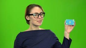 Το κορίτσι διαφημίζει μια κάρτα και παρουσιάζει τους αντίχειρες πράσινη οθόνη απόθεμα βίντεο