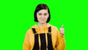 Το κορίτσι διαφημίζει τα αγαθά και παρουσιάζει τους αντίχειρες πράσινη οθόνη απόθεμα βίντεο