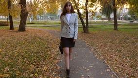 Το κορίτσι δικηγόρων με το μαύρο χαρτοφύλακα πηγαίνει πορεία στο πάρκο φθινοπώρου απόθεμα βίντεο